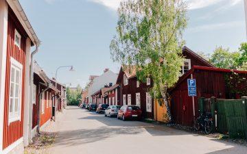 Parkerade bilar längs med lummig gågata i centrala Falun