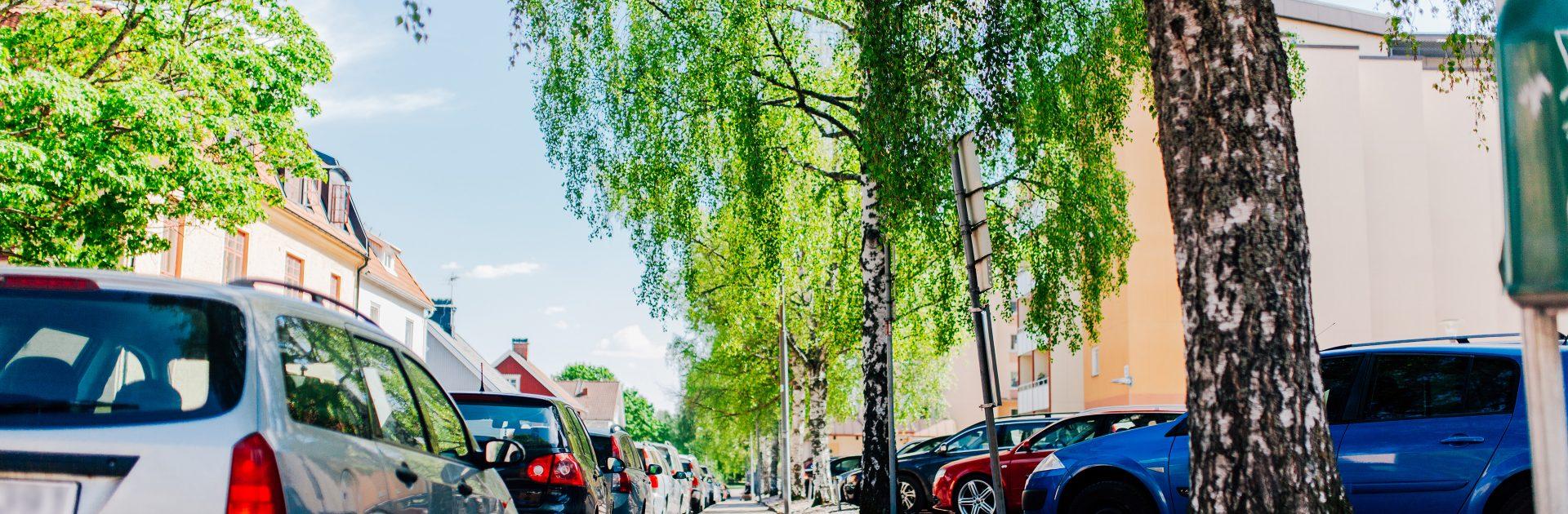 Parkerade bilar på var sida i ett grönskande Falun