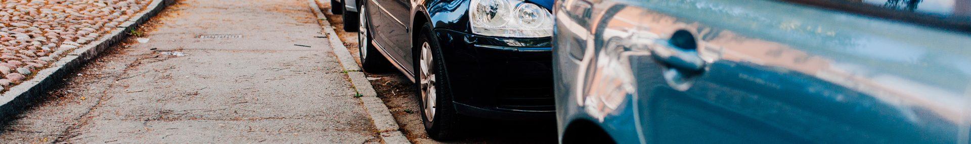 Två parkerade bilar längs med trottoarkanten